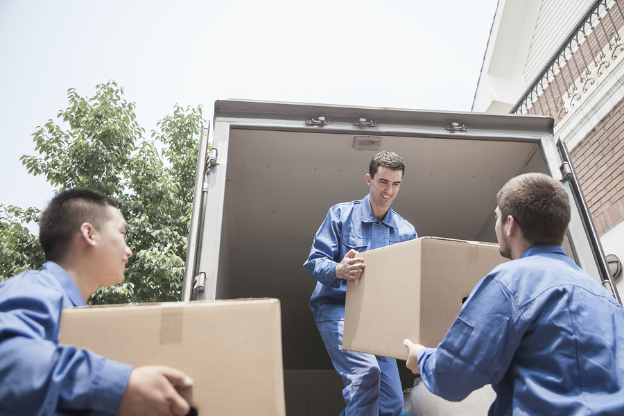 Movers unloading a moving van and passing a cardboard box